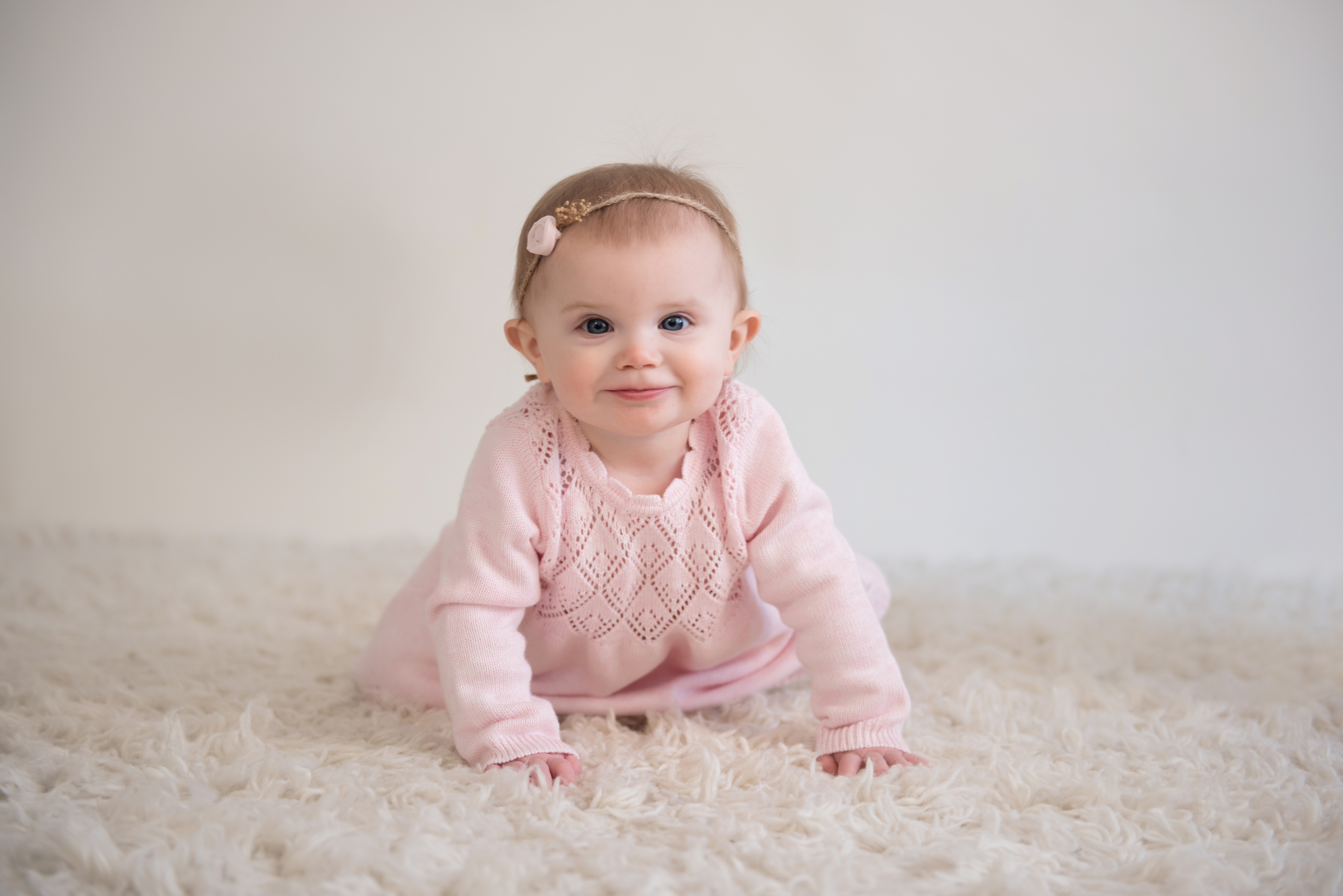 one year old girl crawling in pink