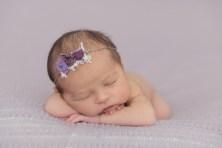 baby head on hands in purple