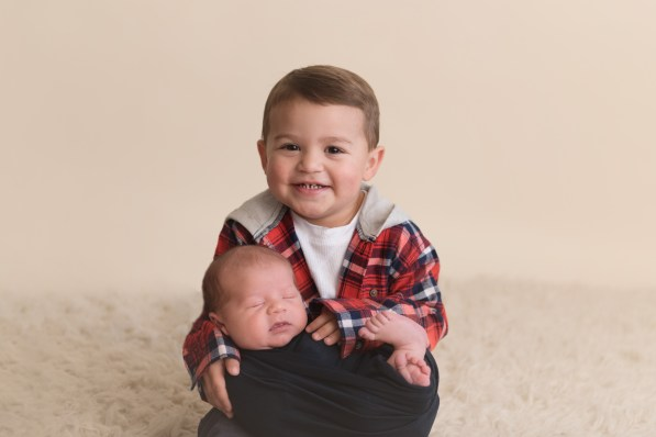 big brother holding new baby