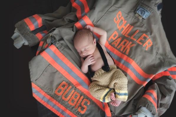 newborn on dads firefighter jacket