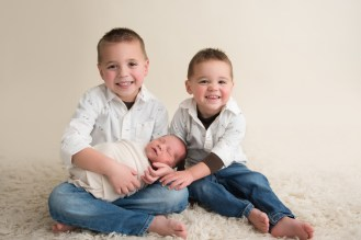 two brothers holding their new baby