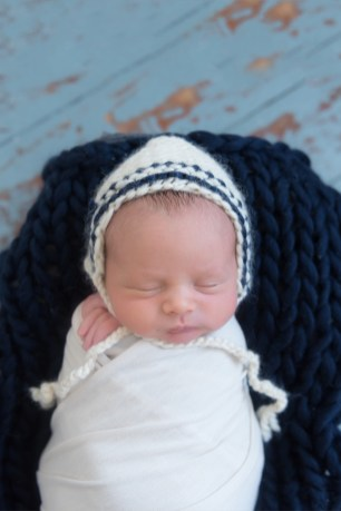 baby wrapped in navy and cream bonnet