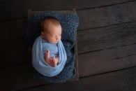 baby wrapped in blue on dark wood