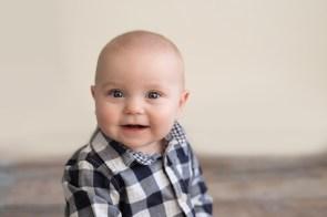 smiling baby boy in plaid shirt