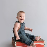 baby with rolls sitting on coke crate
