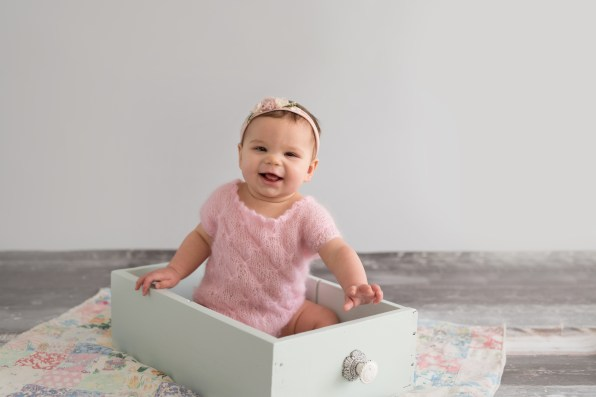 baby girl sitting in vintage drawer mint