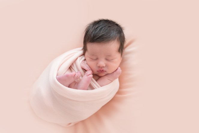 baby wrapped in peach