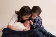 sibling kissing new baby