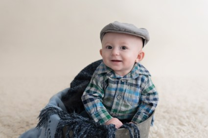 smiling baby boy in a hat in a bucket