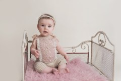 baby girl in vintage romper on iron bed
