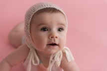 close up of baby girl in knit bonnet
