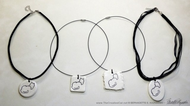 "All four pendants"". 1"" x 1"" round on flocked cord; 1"" x 1"" square on wire cord; 1.5"" x 1.5"" irregular on wire cord; 1"" x 1.5"" oval on multi-strand cord."