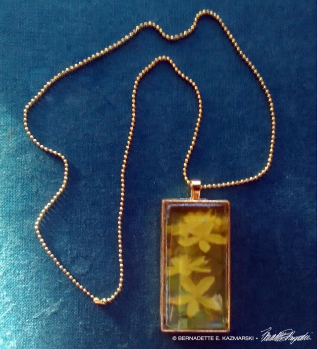 St. John's Wort cabochon pendant on gold chain.