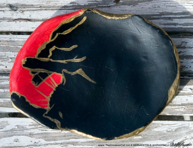 """Black and red with gold, """"The Big Nap"""" decorative dish."""
