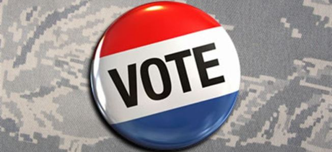 Red white and blue vote button on grey camouflage background.