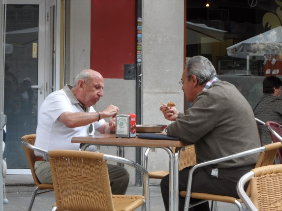 Two spanish men enjoying Paella