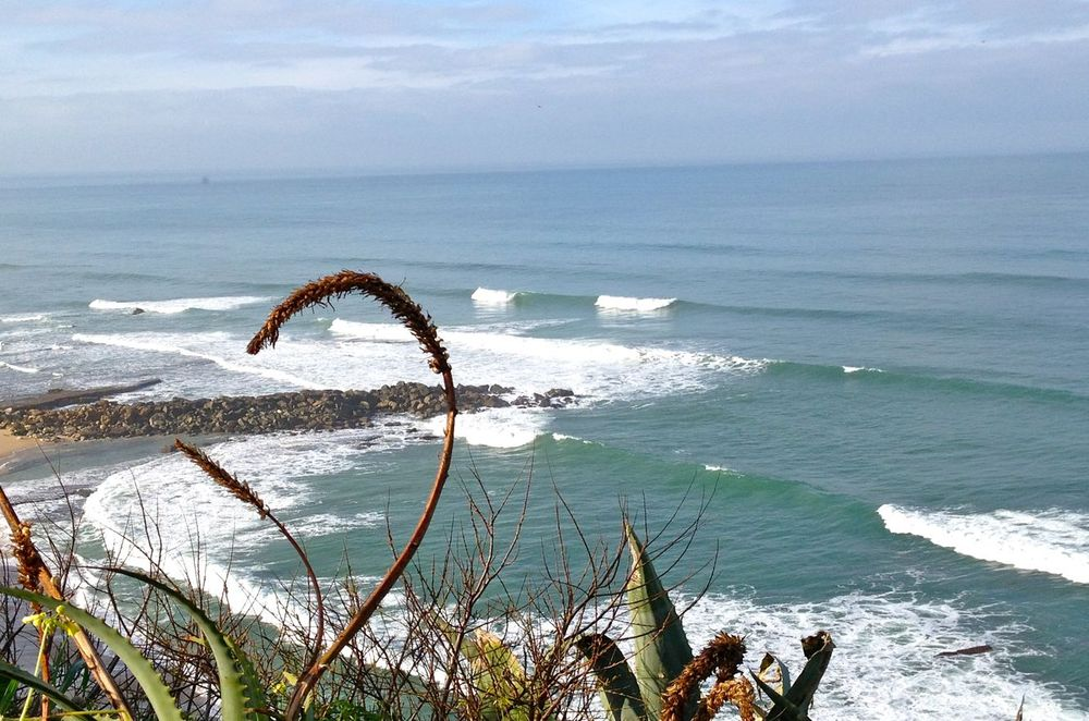 View from the hill on the surfing waves on the beach in Ericeira Portugal