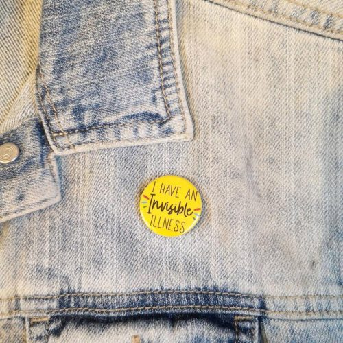 "A denim jacket with a bright yellow badge on it. The badge reads ""I have an invisible illness""."
