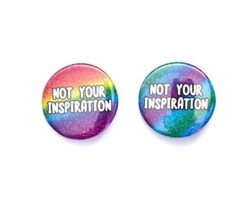 "Two badges on a white background which each say ""not your inspiration"". The left is a glittery rainbow, while the right is glittery green, blue and purple."