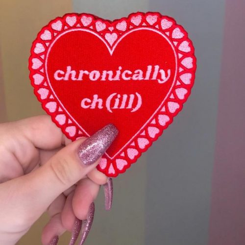 "A heart shaped patch featuring the words ""chronically chill"""