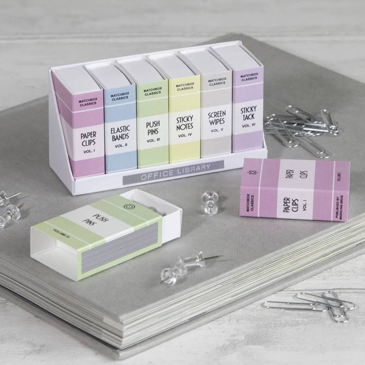 A rack of match boxes in pastel colours which have been designed to look like office files. They contain pins, elastic bands, etc