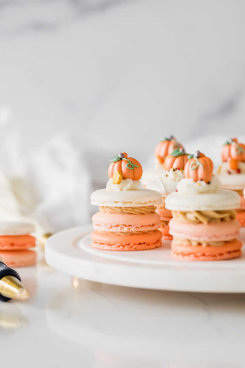 A recipe for pumpkin spice latte french macaron stacks topped with autumn decorations from Wilton. Dairy & gluten free