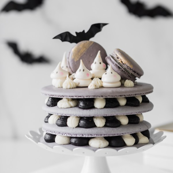 A Halloween themed french macaron cake recipe with ghost meringues and black cocoa frosting. Dairy & Gluten Free