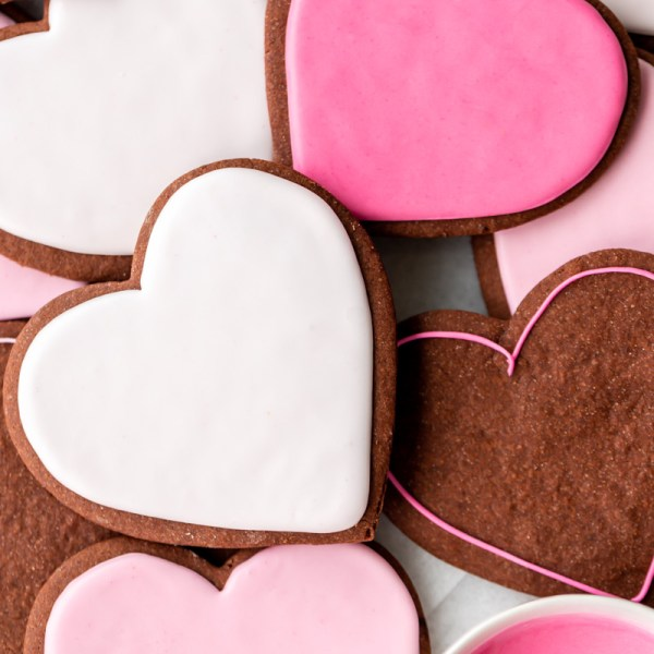 Soft and delicious chocolate cutout sugar cookies decorated with vanilla royal icing. Recipe and decorating video. Perfect for Valentine's Day