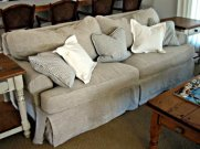 Sofa with washable, natural linen custom slipcovers; washable cotton ticking stripe pillows.