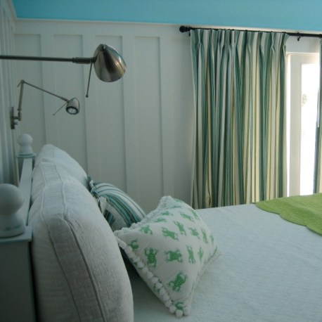 The extra tall bed has wall-mounted lighting. Custom curtains in a blue and green ticking stripe and a Froggy pillow keep it beachy.