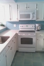 Kitchen cabinets were painted, a glass subway tile backsplash was installed with new quartz countertops