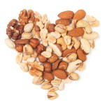 Various nuts forming heart shape on white background