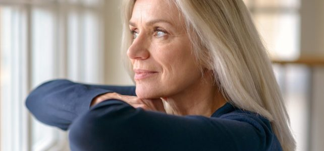 woman with content expression looking out window_dietitian positively nourishing nutrition consulting