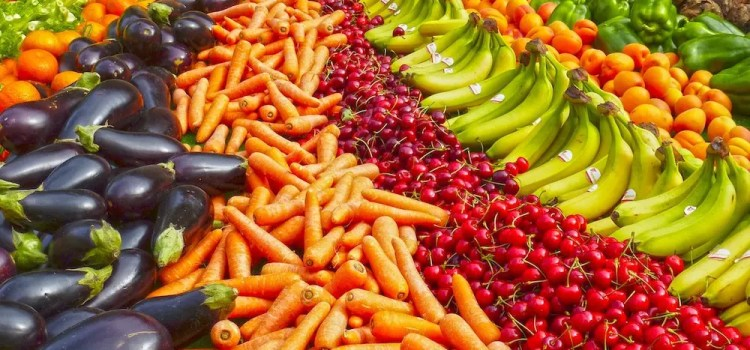 variety fruits and vegetables laid out in rainbow