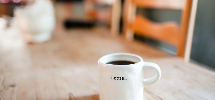 white coffee mug with text Begin sitting on wooden kitchen table