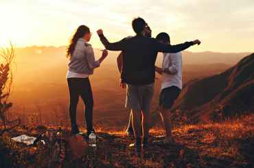 four person standing at top of grassy mountain