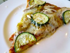 Cheese pizza topped with chicken and zucchini