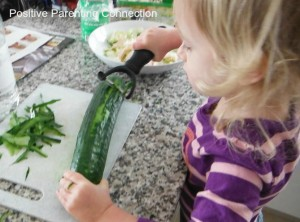 My daughter helping peel cucumber for our salad.