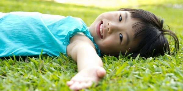 kid doing body scan in grass - Teaching Essential Mindfulness Practices and Skills body scan kids
