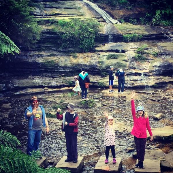 Autism family posing for photo on rocks at bottom of Katoomba Falls - positivespecialneedsparenting.com