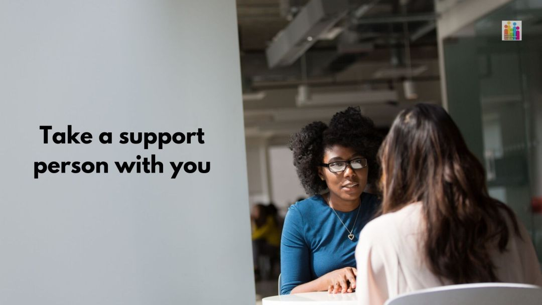 """Image of two women sitting across from each other at a table. One woman has long dark hair while the other has shorter hair and glasses. Text next to them reads, """"take a support person with you."""""""