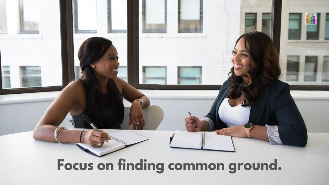 """Image of two African American women, both with dark hair, smiling at each other at a desk. They both have open notebooks in front of them with a pen in their hand with the text """"focus on finding common ground."""""""