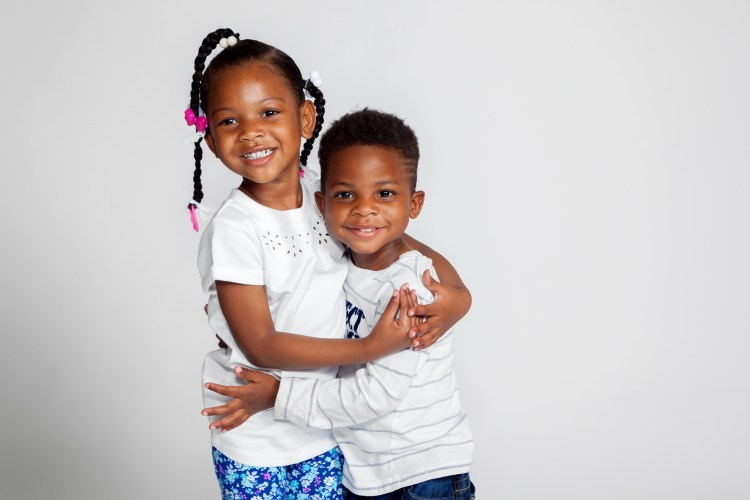 A young African American girl in braids hugs her little brother.  Both are smiling for their portrait against a white backdrop.