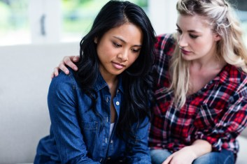 Young woman consoling depressed female friend