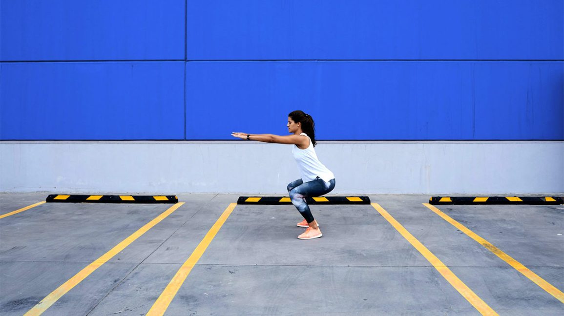 woman doing squat variations outside in front of a blue wall