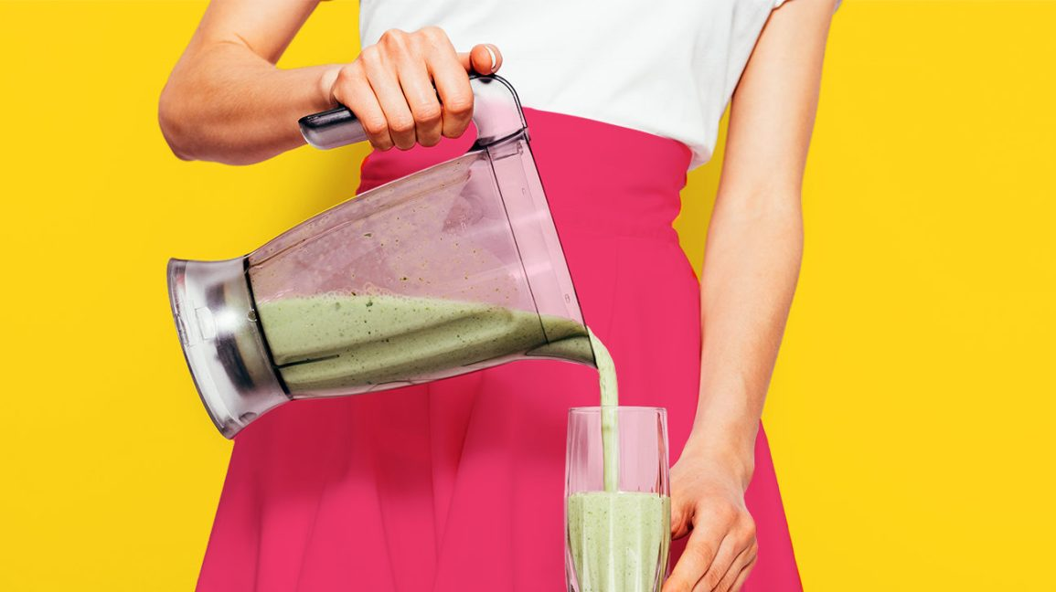 woman in a pink skirt pouring a smoothie