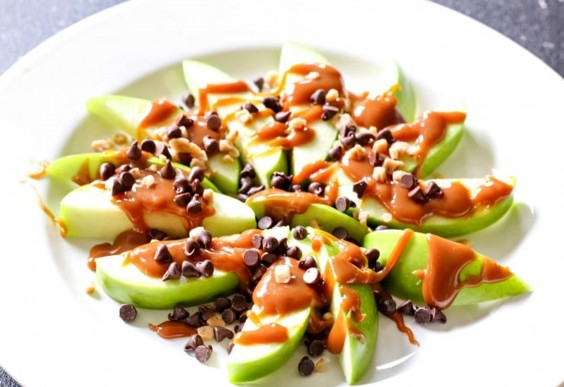 A plate of apple nachos covered in caramel sauce and chocolate chips