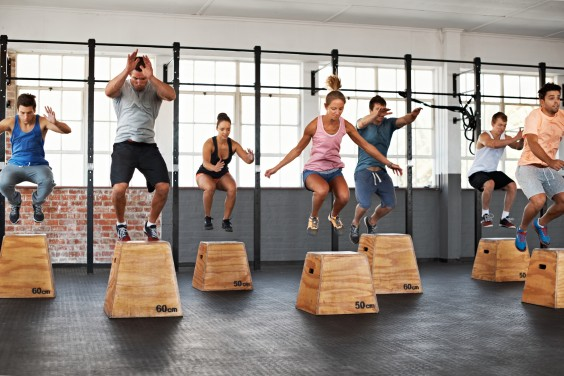 Men and women box jumping in a fitness class
