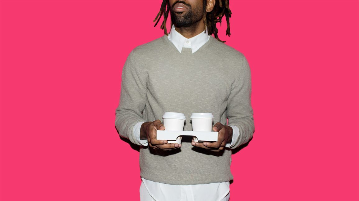 Stylish man with dreads and a beard holding two cups of to-go coffee against a hot pink background.