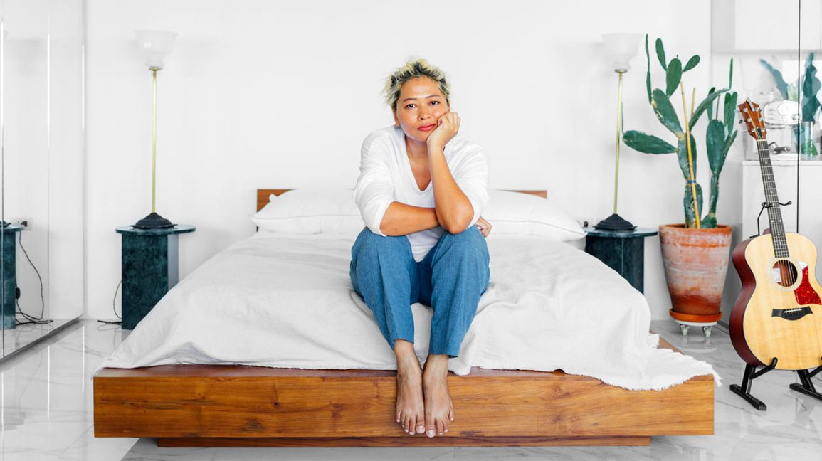 woman sitting on a bed looking concerned